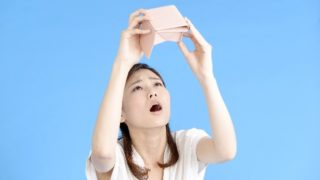 空っぽの財布を覗く女性