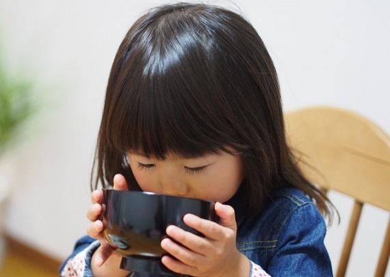 美味しそうにお味噌汁を飲む子供