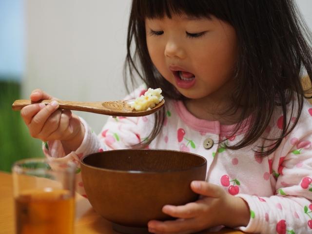 パジャマで食事する子供